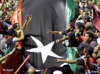 Libyans holding a huge flag celebrate overrunning Moammar Gadhafi's main compound Bab al-Aziziya in Tripoli, Libya, early Wednesday, Aug. 24, 2011.