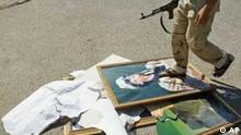 A Libyan rebel fighter stamps on a portrait of Moammar Gadhafi , in Tripoli, Libya, Thursday, Aug. 25, 2011. Libya's rebel leadership has offered a 2 million dollar bounty on Gadhafi's head, but the autocrat has refused to surrender as his 42-year regime crumbles, fleeing to an unknown destination. Speaking to a local television channel Wednesday, apparently by phone, Gadhafi vowed from hiding to fight on until victory or martyrdom. (Foto:Francois Mori/AP/dapd)