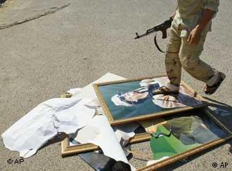 Aufständischer tritt Porträtbild Gaddafis (Foto: AP)