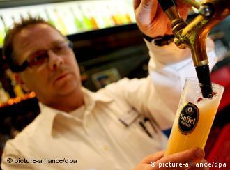 A waiter pours out a glass of Kölsch