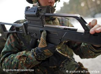 A soldier holds a German weapon
