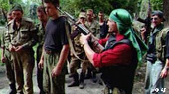 A Chechen fighter points his rifle to the head of a Russian prisoner of war outside the Chechen captial of Grozny Thursday, August 15, 1996. Russian security chief Alexander Lebed, armed with sweeping new powers to end the disastrous war in Chechnya, headed for a meeting with rebel leaders Thursday. Lebed was on his second peace-making mission to Chechnya in five days. His first produced talks between the top commanders for both sides that partially quelled the bloody battle for Grozny. (AP Photo/Mindaugas Kulbis)