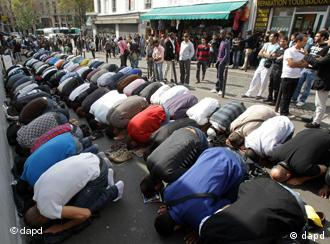 Muslims pray on a sidewalk during Friday prayers in Paris