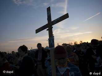 Worshippers with a crucifix in the sunset