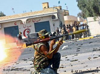 In this photo released by China's Xinhua News Agency, a fighter of Libya's ruling National Transitional Council (NTC) fires a RPG rocket at pro-Gadhafi forces during heavy battles at the entrance of Al-Etha'a street, about 7 kilometers (4 milers) from the heart of Sirte, Libya, Saturday, Sept. 24, 2011. With NATO jets roaring overhead, Libya's revolutionary forces have been fighting their way into Moammar Gadhafi's hometown in the first significant push into the stubborn stronghold in about a week. (AP Photo/Xinhua, Amru Salahuddien) NO SALES