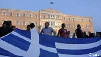 Protesters hold a giant flag outside the Greek parliament during a protest against austerity measures, in Athens
