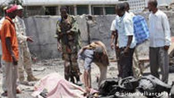 epa02950365 People gather around a body of a car bomb explosion victim in war-torn Somalia's capital Mogadishu, 04 October 2011. Reports state that more than 50 people have been killed after a vehicle exploded in front of the Ministry of Education building. Al Qaeda-linked Islamic militia al-Shabab has claimed responsibility for the deadly attack. EPA/ELYAS AHMED
