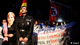 Actors impersonating German Chancellor Angela Merkel and former German dictator Adolf Hitler stand in front of demonstrators holding up banners and a Nazi flag during a during a protest outside the German embassy in the Greek capital Athens (Foto:Kostas Tsironis/AP/dapd)