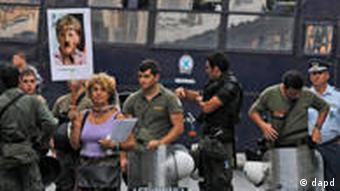 A woman holds up a placard with the image of German Chancellor Angela Merkel during a protest outside the German embassy in the Greek capital Athens, on Thursday Oct. 6, 2011. The placard reads, Europe will become German. The small group of protesters said Germany must pay Greece reparations for its occupation of the country during WWII before Greece pays off its debts. (Foto:Kostas Tsironis/AP/dapd)