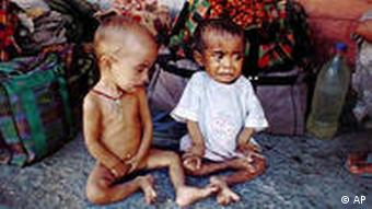 Two emaciated Bangladeshi children wait among hundreds of other refugees at a rail station in New Jalpaiguri, India along the Bangladesh border to be returned to their country Thursday October 7, 1999. 253 refugees were captured by Indian authorities and sent back to their homeland. (AP Photo/Tarun Das)