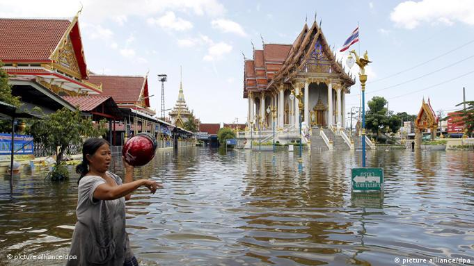 Thai resident wades through floodwaters at submerged Buddhist temple in Bangkok, Thailand, October 2011