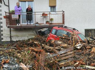 Two residents view wreckage caused by flooding in Brugnato, Liguria