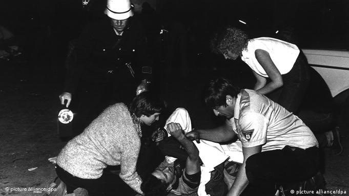 Emergency personnel and festival attendees attempt to help injured person after nail bomb explodes at Oktoberfest, Sep. 26, 1980
