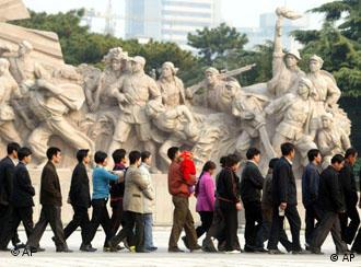 ** TO GO WITH THE STORY SLUGGED CHINA THE GREAT PARADOX ** People walk past statues of communist revolutionaries as they file into the mausoleum of late leader Mao Zedong in Beijing's Tiananmen Square, Oct. 29, 2002. As it convenes a congress that is expected to install a new generation of leaders, the ruling Communist Party is trying to transform itself in order to stay relevant amid economic and social reforms that it unleashed. (AP Photo/Greg Baker)