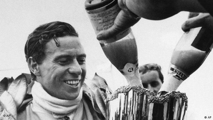 Jim Clark of Scotland, holds the winners trophy and watches as champagne is poured into it after he had won the first Australian race of the 1968 Tasman Cup Series at Surfer's Paradise, Queensland, Australia, on Feb. 14, 1968. (AP Photo)