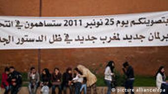 Junge Menschen unter einem Wahlplakat in Marokko (Foto: dpa)