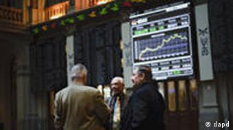 Brokers talk in front of the main display at the Stock Exchange in Madrid