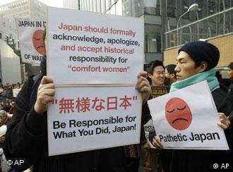 Protesters hold signs during their 1,000th weekly rally to demand an official apology and compensation for wartime sex slaves from the Japanese government