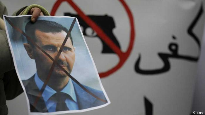 A Syrian immigrant holds a crossed out depiction of Syrian President Bashar al-Assad during a rally against his regime in front of the Syrian embassy in Belgrade, Serbia, Friday, Dec. 23, 2011. (Foto:Darko Vojinovic/AP/dapd)