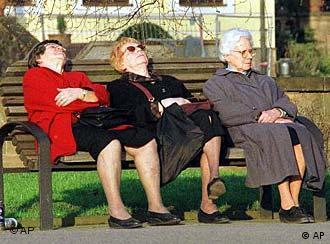 Drei alte Damen sitzen auf einer Bank und genießen die Sonne.
