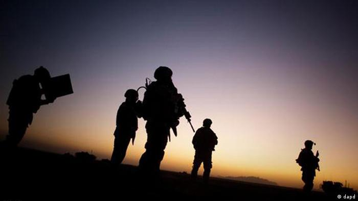 US troops (in silhouette) in Afghanistan at dusk