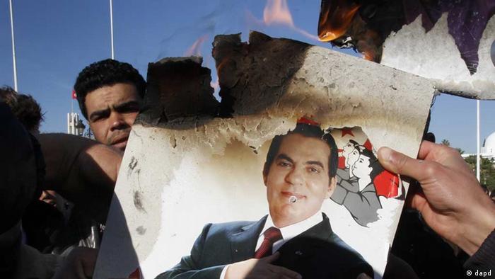 Protester burns a picture of Zine El Abidine Ben Ali