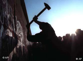 A man hammering away at the Berlin Wall in November 1989