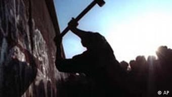 A man hammers away at the Berlin Wall on Nov. 12, 1989