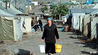 A woman carries buckets of water at a camp for Chechen refugees