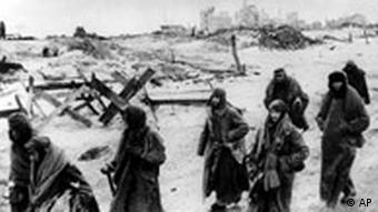 German soldiers, their uniforms tattered from the battle, making their way in the bitter cold through the ruins of Stalingrad.