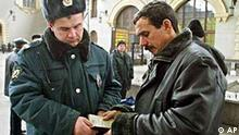 A police officer, left, checks documents of a man at a railway terminal in downtown Moscow, Thursday, Oct. 31, 2002. Many Chechens and other dark-skinned people from the Caucasus region with no known connection to the hostage crisis have been caught up in the police dragnet. Chechens in the Russian capital say they've been subjected to more unannounced police visits, document checks, and harassment in the wake of the theater hostage drama, which ended Saturday when Russian troops stormed the theater. (AP Photo/Alexei Sazonov)