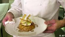 French chef Christian Le Squer presents a cod dish in the kitchen of the Ledoyen restaurant, Tuesday Feb.12, 2002 in Paris. The restaurant now gets a prestigious three-star rating in the famous French food lover's bible Guide Rouge 2002 (Red Guide), formerly known as the Guide Michelin, which will be available on March 1 2002. (AP PHOTO/ Francois Mori)