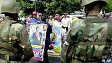 A street vendor holds pictures of President Hugo Chavez between a line of soldiers and supporters of Chavez, near the Petroleos de Venezuela SA main offices in Caracas, Venezuela, Thursday, Dec. 5, 2002. (AP Photo/Fernando Llano)