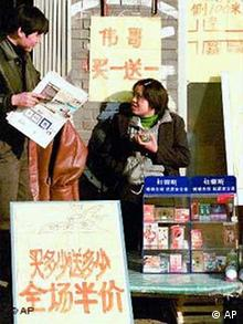 A vendor sits by a display of condoms and sale signs including one that translates as buy one, get one free for Viagra, outside a sex shop in Beijing in this Jan. 12, 2001 file photo. Twelve Chinese companies are challenging Pfizer Inc.'s exclusive rights to the little blue pill in China, a potentially huge market where men have for centuries sought drugs to boost sexual performance. (AP Photo/Str)