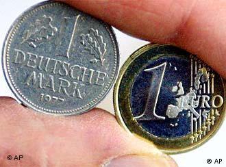 Auf einem Archivbild vom 14. Dezember 2001 haelt ein Angestellter der Landeszentralbank in Bremen eine D-Mark und eine Euro-Muenze nebeneinander. Wie die Gesellschaft fuer Deutsche Sprache (GfdS) am Freitag, 20. Dezember 2002, in Wiesbaden bekannt gab, ist 'Teuro' das Wort Jahres 2002. Das Wort bringe das Gefuehl vieler Menschen zum Ausdruck, dass im Zuge der Euro-Bargeldeinfuehrung zum 1. Januar 2002 vieles teurer geworden sei.