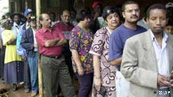 Kenyans of African and Asian Communities wait in a line to vote at Westlands Primary School, Nairobi, Kenya, Friday, Dec. 27, 2002, in a nationwide election in which more than 10.5 million voters are expected to participate. Uhuru Kenyatta, Mwai Kibaki, Simeon Nyachae, James Orengo and David Waweru Ng'ethe are running for the president, but they also have to win their parliamentary seats as well. (AP Photo/Sayyid Azim)