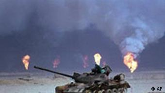 A destroyed Iraqi tank rests near a series of oil well fires during the Gulf War