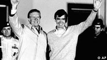Former President Jimmy Carter waves as he looks at former hostage Bruce Laingen, from Bethesda, MD, former Charge d'Affaire at the U.S. Embassy in Tehran, on the balcony of the U.S. Air Force hospital, January 22, 1981 in Wiesbaden, Germany. Carter paid a three hour visit to the hostages from Iran at the hospital, where they are lodged after 444 days of captivity. (AP Photo)