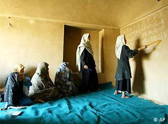 A woman reads Arabic numbers to an adult women's literacy class