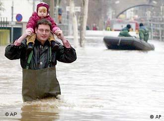 A man carries his daugher along a flooded street in Bonn