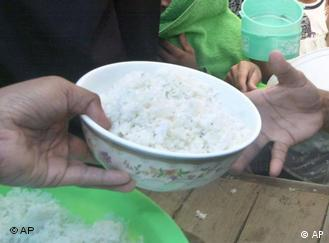 Child reaching out for bowl of rice offered by an adult