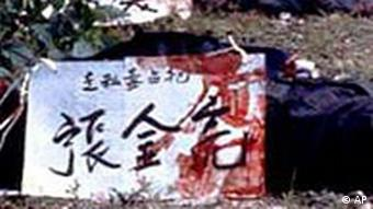 ...those to be executioned in China wear their names on placards around their necks. This picture shows a person who has been executed. In the foreground: the person's placard