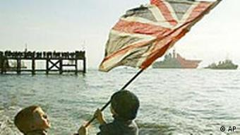 Young boys wave a Union flag as the British Aircraft Carrier Ark Royal is pulled by a tug as it leaves Portsmouth