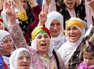 Kurdish women make V-victory signs as they chant slogans during a demonstration in Istanbul