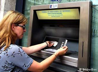 A woman in Italy withdraws money from an ATM