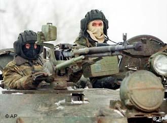 Masked Russian Interior ministry troops soldiers look on while patrolling atop a tank