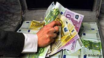 A hand grabs at a pile of euro bills