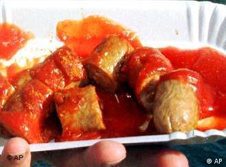 eine Hand hält eine weiße Pappschale mit Wurstscheiben, roter Soße und Currypulver