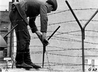 Soldado coloca arame farpado sobre o Muro