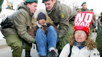 Polizisten tragen einen Demonstranten von der Zufahrtsstraße zum Hauptquartier der US-Streitkräfte in Stuttgart